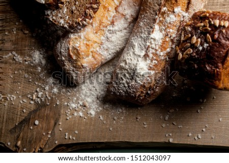 fresh bread on wooden background. Freshly baked traditional bread with flour on wooden table. Fresh bread with flour on wooden table. fresh baguette with sunflower seeds and flour #1512043097