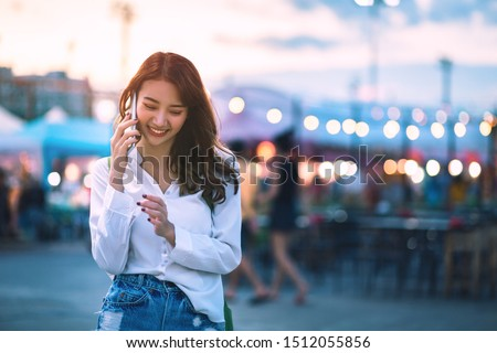 Happy young travel asian woman using smartphone and relax on street market against light bokeh background at dusk in Bangkok, Thailand, Travel vacation city concept #1512055856