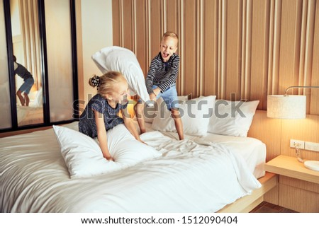 Adroable little brother and sister laughing while having a pillow fight together on their bed at home #1512090404