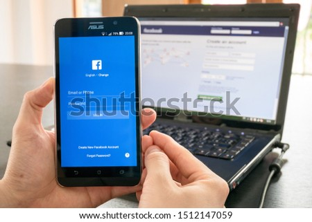 CHIANG MAI, THAILAND - JULY 8, 2017: man hand holding mobile phone with screen shot of Facebook application. Facebook is an American online social media and social networking service company. #1512147059