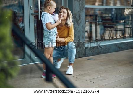 Cheerful lady smiling and watching her daughter drinking milkshake #1512169274