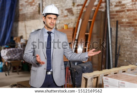 Portrait of friendly and welcoming man in suit and helmet at construction site #1512169562