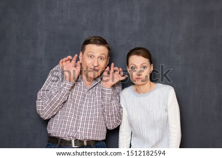 Studio waist-up portrait of funny caucasian young adult couple, grimacing and making foolish faces with surprised absurd expression, fooling and having fun together, standing over gray background #1512182594