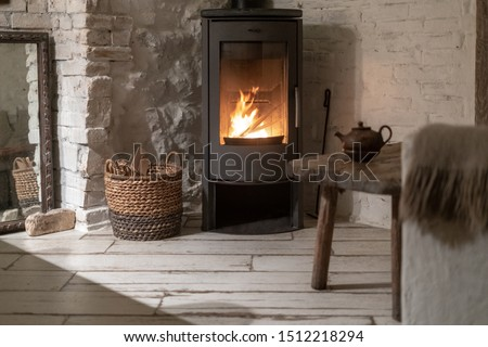 Wicker basket with firewood near fire chimney. Wood stove fireplace with metal body and glass door in comfort house with cozy interior in room #1512218294