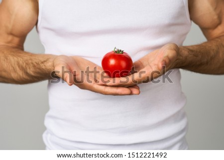 a man holds a red tomato in his hands in a white T-shirt #1512221492