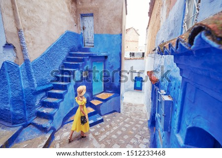 Colorful traveling by Morocco. Young woman in yellow dress walking in  medina of  blue city Chefchaouen. Royalty-Free Stock Photo #1512233468