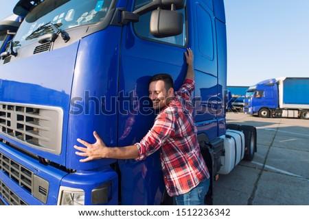 Truck driver loves his job. Professional trucker driver hugging his truck cabin loving his job. #1512236342