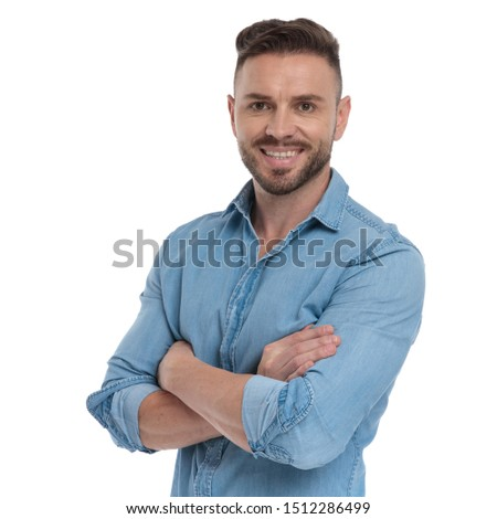 beautiful casual man with blue shirt is standing with arms crossed happy on white studio background #1512286499