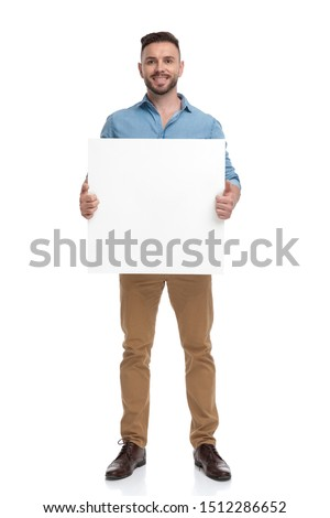 young casual man with blue shirt is standing with a billboard on his hands happy on white studio background #1512286652