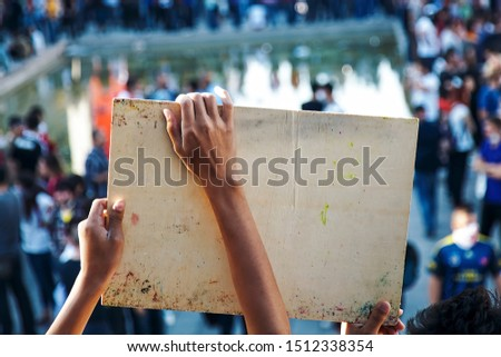 Hands of a young Asian male holds a protest sign against the crowd. View from back