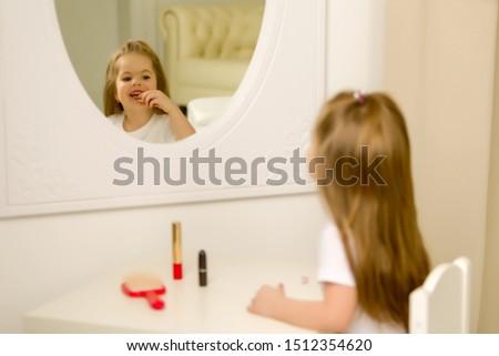 A little girl near the mirror paints lipstick lips #1512354620