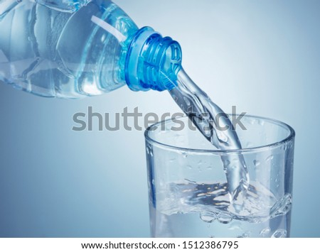 pouring clean water from plastic bottle into glass on blue background #1512386795