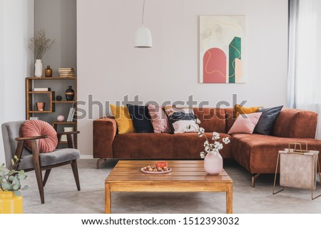 Flowers in vase on wooden coffee table in fashionable living room interior with brown corner sofa with pillows and abstract painting on the wall #1512393032