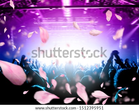 Concert crowd under a rain of confetti from above, background is a lit stage #1512395951