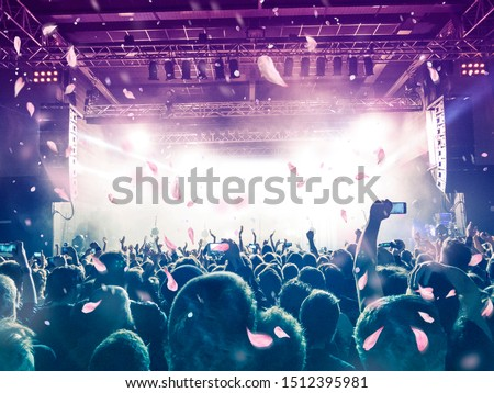 Concert crowd under a rain of confetti from above, background is a lit stage #1512395981