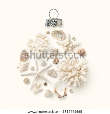 Christmas in July / at the beach / in the southern hemisphere concept with holiday ornament made of shells, starfish and corals on a cream colored background, flat lay / top view, copy space for text #1512441665