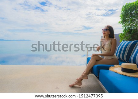 Portrait young asian woman relax smile happy around swimming pool in hotel and resort for holiday vacation travel concept #1512477395