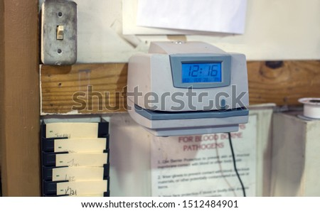 An old fashioned time clock is mounted on a factory wall, with time cards and other important notices and posters #1512484901