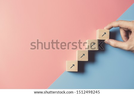 Business concept growth success process, Close up man hand arranging wood block stacking as step stair on paper blue and pink background, copy space. Royalty-Free Stock Photo #1512498245