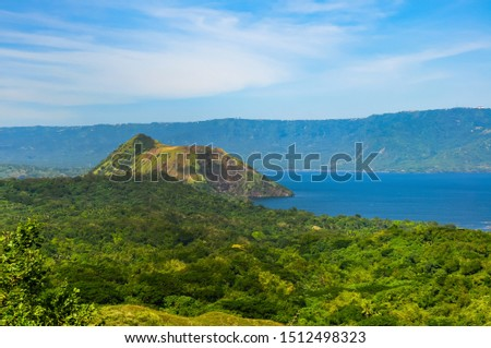 Taal Volcano in Tagaytay city, Philippines. As one of the most active volcanoes in the country. Taal Volcano had exploded 33 times already since 1572. Blue sky background and greenish foreground. #1512498323