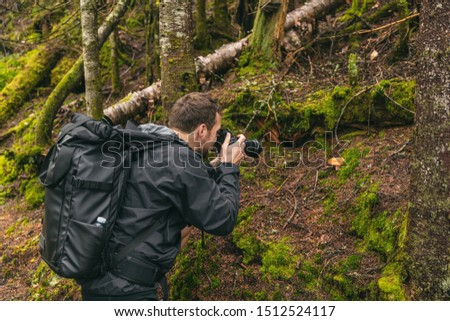 Nature still photography photographer man with professional slr camera taking picture of wild mushroom in forest during trail hike.