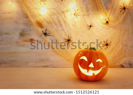 holidays halloween concept image. Pumpkin, spiders over wooden table