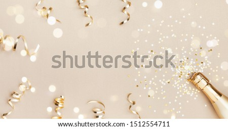Champagne bottle with confetti stars, bokeh decoration and party streamers on golden background. Christmas, birthday or wedding concept. Flat lay. #1512554711