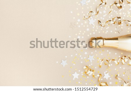 Golden champagne bottle with confetti stars and party streamers top view. Christmas, birthday or wedding background. Flat lay style. #1512554729