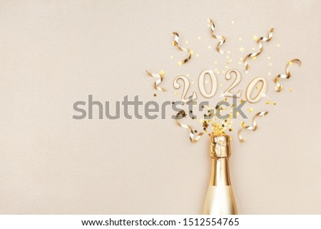 Creative Christmas and New Year composition with golden champagne bottle, party streamers, confetti stars and 2020 numbers. Flat lay style. #1512554765