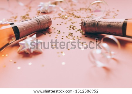 Christmas or New Year composition with bottles of rose champagne and golden shiny sparkle star confetti on pastel pink background, side view. Party Celebration creative concept #1512586952