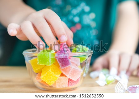 Closeup hands of a little child taking a piece of jelly cube with sugar in a glass bowl. Snacks time, Sugary treats, Party, Kids favorite, Unhealthy, Cavity, Sugar addiction, Sweetness, ADHD, Drug. #1512652550