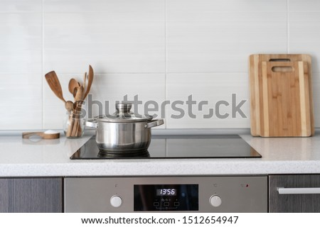 Black ceramic induction stove with timer on control panel and saucepan on top. Contemporary home with modern interior, built in kitchen appliance and white tile on wall with copy space #1512654947