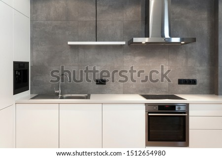 Modern interior design at white contemporary kitchen in loft style. Glossy cabinet with built in household appliance, electric stove, oven, sink on worktop and extractor hood on grey wall #1512654980