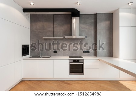 White cupboard with built in household appliance, electric stove, oven, sink on worktop, wooden laminate on floor and extractor hood on grey wall. House with modern interior at contemporary kitchen #1512654986