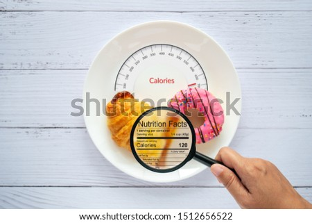 Calories counting, food control and consumer nutrition facts label concept. doughnut and croissant on white plate with tongue scales for Calories measuring and magnifying glass zoom for nutrition fact #1512656522
