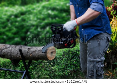 The carpenter man used a black saw to cut the wood. #1512661778