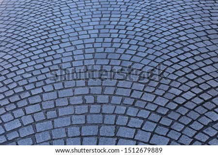Close up view of a street pavement made of cobblestones. Abstract urban picture with black curved lines and grey squares. Rough surface with curving shapes. Detail of a road in a french city. #1512679889