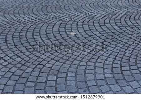 Close up view of a street pavement made of cobblestones. Abstract urban picture with black curved lines and grey squares. Rough surface with curving shapes. Detail of a road in a french city. #1512679901