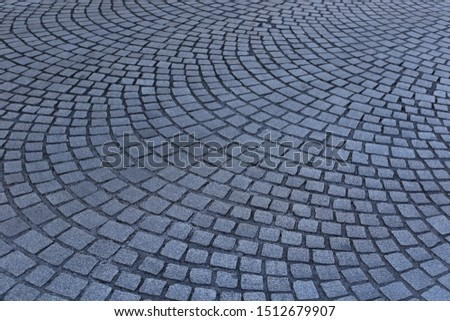 Close up view of a street pavement made of cobblestones. Abstract urban picture with black curved lines and grey squares. Rough surface with curving shapes. Detail of a road in a french city. #1512679907
