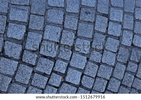 Close up view of a street pavement made of cobblestones. Abstract urban picture with black curved lines and grey squares. Rough surface with curving shapes. Detail of a road in a french city. #1512679916