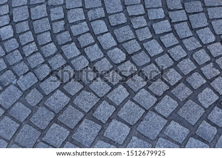Close up view of a street pavement made of cobblestones. Abstract urban picture with black curved lines and grey squares. Rough surface with curving shapes. Detail of a road in a french city. #1512679925