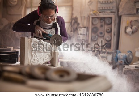Female worker in an art workshop, grinding a piece of white marble, sculptor creating a stone sculpture, cloud of dust flying away, stonemasonry and stonecraft Royalty-Free Stock Photo #1512680780