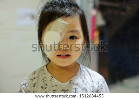 A cute Asian girl with on eye covered with white plaster after surgery for hordeolum infection on her eyelid, happy and smiling.  #1512684455