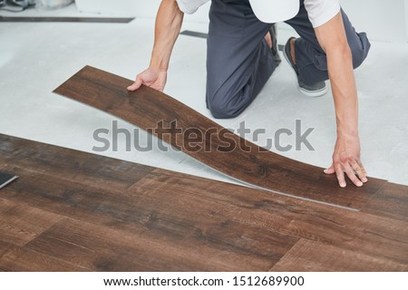 worker joining vinyl floor covering at home renovation #1512689900