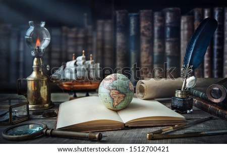 Exploration and nautical theme grunge background. Globe, telescope, divider, old coins, shell, map, book, hourglass, quill pen on wood desk. Columbus Day.  #1512700421
