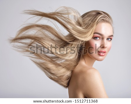 Portrait of a blonde beautiful woman with a long straight light hair. Woman with hair flying in the wind.  Portrait of a beautiful woman with a coral color makeup. Fashion model. Flying hair.  #1512711368