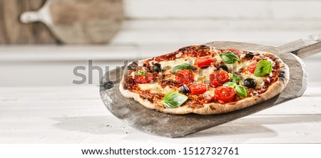 Tasty Margherita Italian Pizza with extra fresh tomato, olives and basil trimmings on an old wooden paddle straight from a wood fired oven, panorama banner format #1512732761