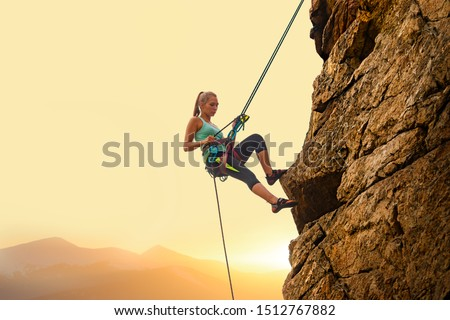 Beautiful Woman Climbing on the High Rock at Foggy Sunset in the Mountains. Adventure and Extreme Sport Concept #1512767882