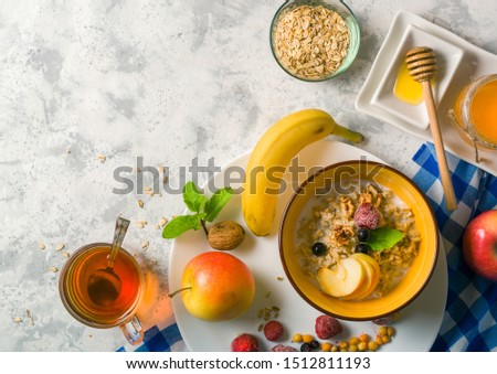 Morning oatmeal for breakfast. Early morning and healthy diet food. Proper nutrition. White stone background. Plenty of space for text. #1512811193