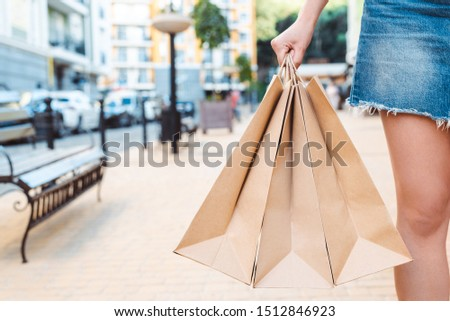 partial view of girl in denim skirt holding paper shopping bags on street #1512846923